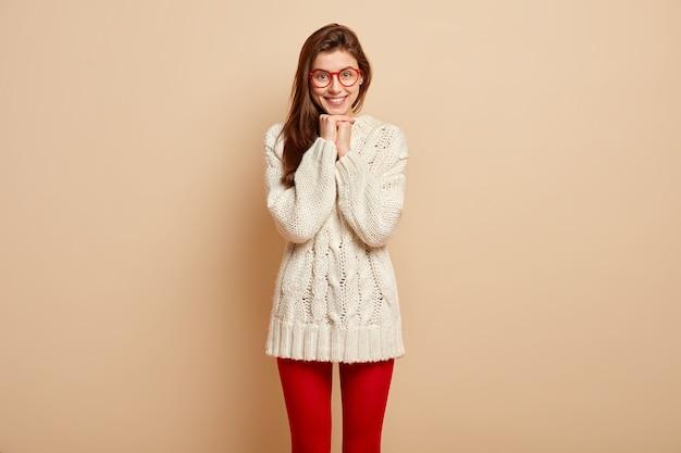 Bruna giovane modello femminile dall'aspetto piacevole tiene le mani unite, sorride positivamente ha un aspetto affascinante, felice di sentire parole piacevoli, indossa un maglione bianco a maniche lunghe e collant rossi, modelli al coperto