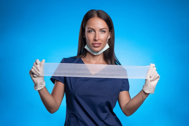 ブルネットは、彼女の顔の保護マスク、青い手術用スーツ、彼女の手に白い医療用手袋を着用し、医療用包帯を手に伸ばして青い背景に立ってポーズをとっています。