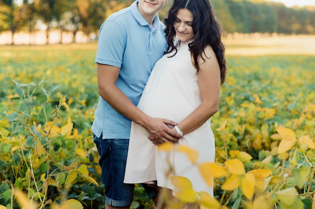 Brunette pregnant lady hugs with her man on yellow field