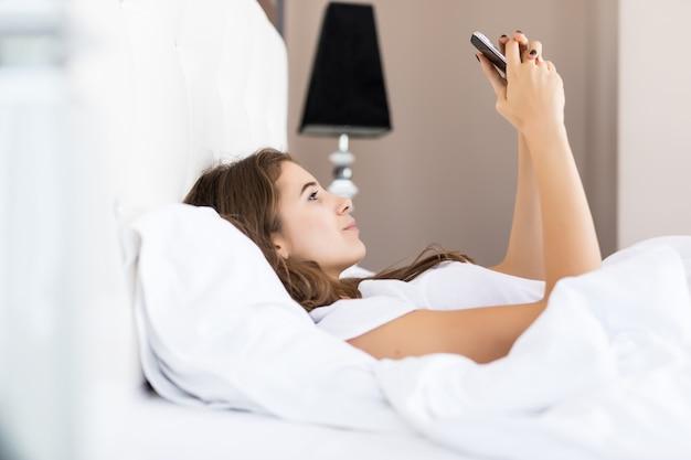 Bella ragazza bruna usa il suo smartphone per leggere le notizie dopo essersi svegliata la mattina nel suo appartamento