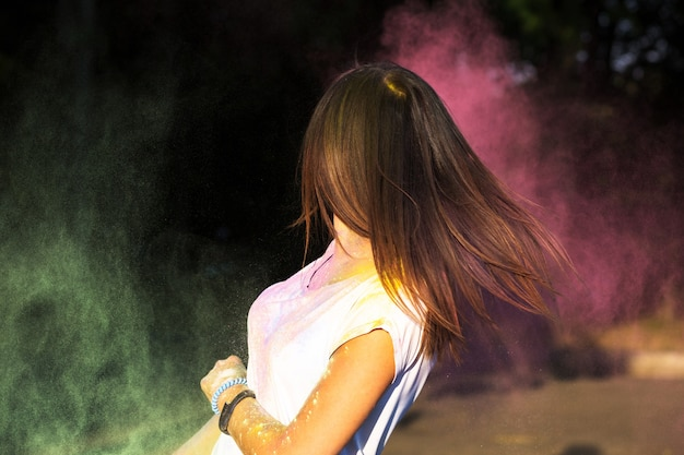 ホーリーパウダーを楽しんでいる動きのある髪のブルネットのかわいいモデル