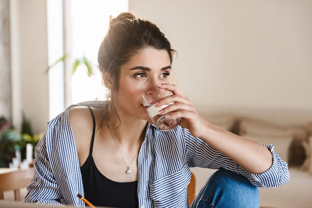 Brunette pretty woman in casual clothing drinking water and using laptop while working in flat