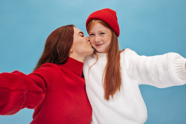 Brunette in red sweater kisses in cheek her small ginger sister in hat and white stylish clothes on isolated wall