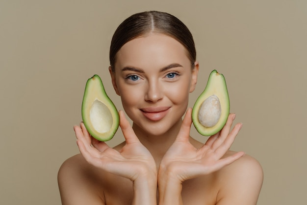 Brunette satisfied european woman holds halves of avocado near face recommends face mask