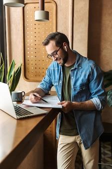 Брюнетка доволен мужчина в очках пишет и использует наушники с ноутбуком во время работы в кафе в помещении