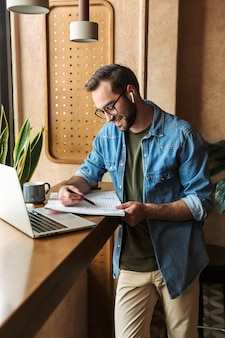 Brunette satisfied man wearing glasses writing and using earpod with laptop while working in cafe indoors