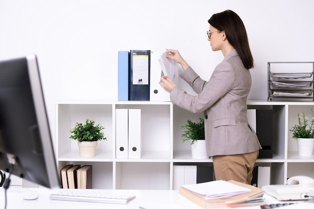 Brunette secretary in jacket cleaning up office room and sorting files in folders