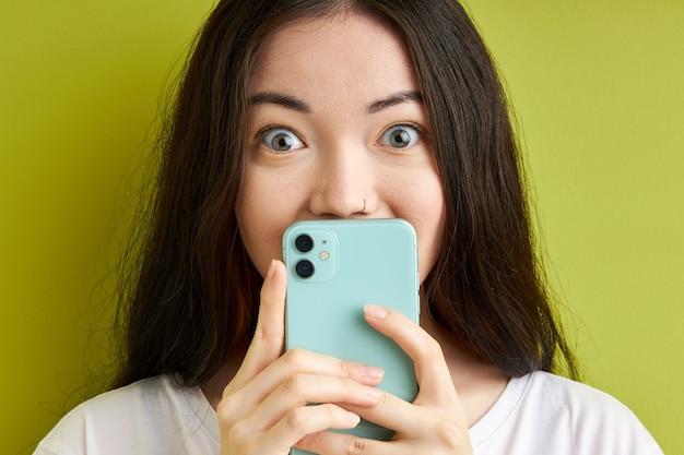 갈색 머리 충격 된 여자는 메시지에 유쾌하게 반응하고, 스마트 폰을 손에 들고, 정보를 숨기고, 녹색 배경 위에 절연
