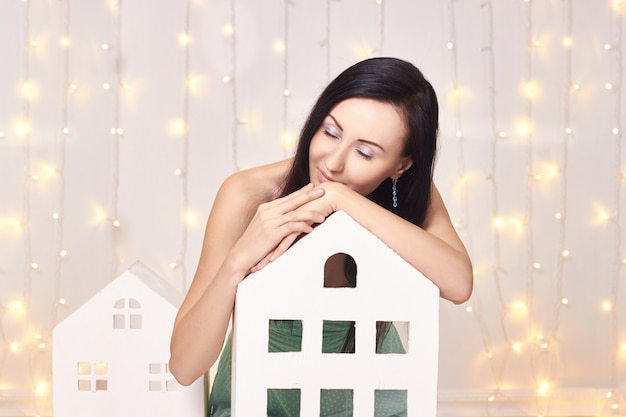 Brunette in short green dress toy houses