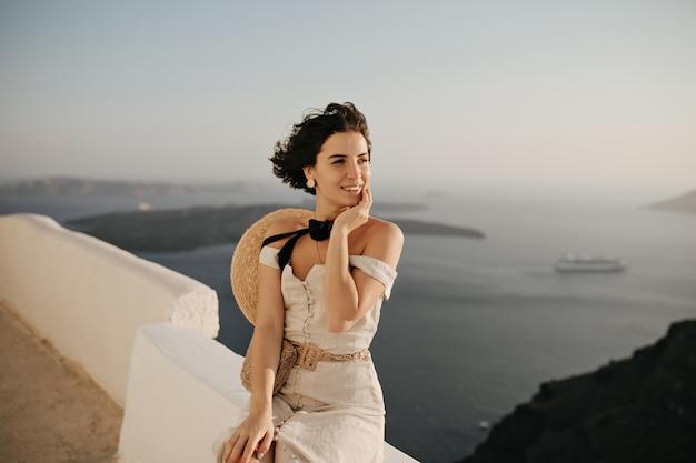 エレガントなベージュのドレスとボーターのブルネットの短い髪の女性は美しい海の景色を楽しんでいます
