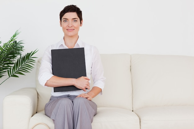 Brunette short-haired woman sitting on a sofa