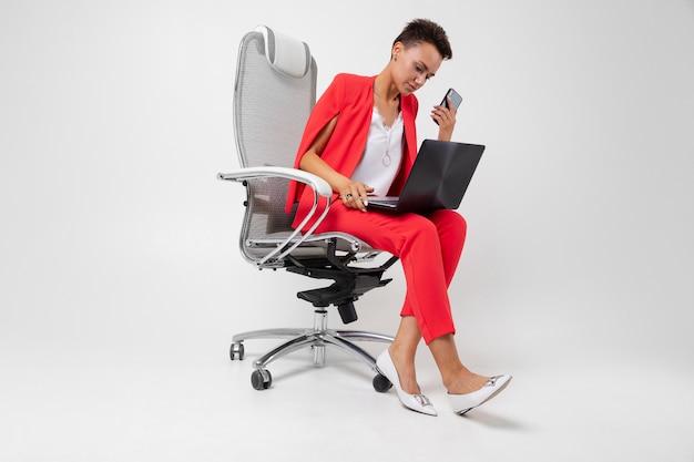 갈색 머리 의자에 앉아 회색에 그녀의 손에 전화로 노트북에 입력
