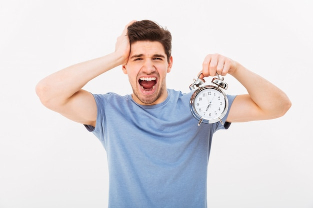 Brunette sleepy young man 30s holding alarm clock and yawning after sleepless night, isolated over white wall
