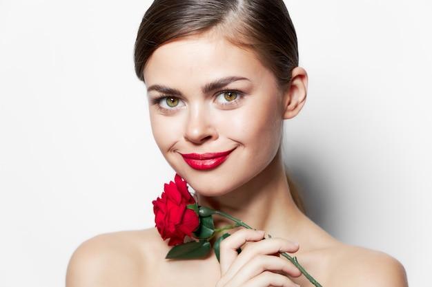 ブルネットの笑顔赤い唇バラの花のギフトのクローズアップ長い髪のトリミングされたビュー