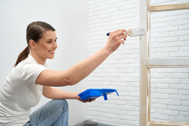 Brunette smiling and painting wooden rack