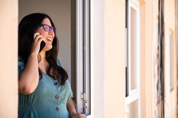 窓に電話を話しているブルネットのスペイン語の女の子