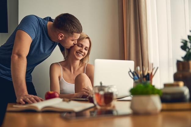 여자가 컴퓨터에서 온라인으로 작업하고 진심으로 웃고있는 동안 그의 여자 친구에게 키스하는 갈색 머리 스포티 한 남자
