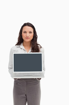 Brunette standing while showing a laptop screen