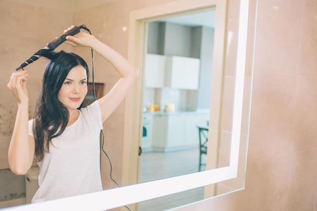 Брюнетка стоит у зеркала и бигуди. она в ванной. женщина держит бигуди обеими руками. она делает прическу.