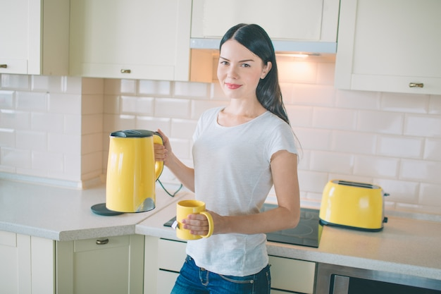 Brunette stands in kitchen. she poses. young woman holds yellow kettle and cup. there is a toaster standing besides her. woman looks very nice.