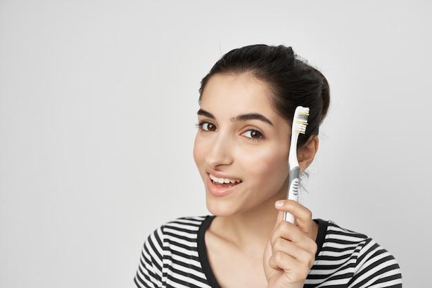 Brunette in a striped tshirt brushing her teeth closeup