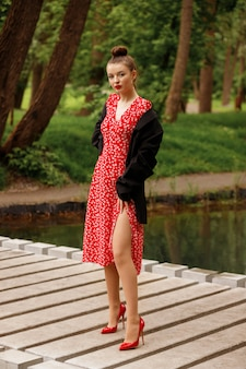 Brunette in stylish clothes for partying and walking. park in summer. model in a red summer dress, jacket, shoes.