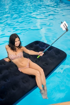 Brunette taking selfie photo on the phone with selfie stick on mattress in pool