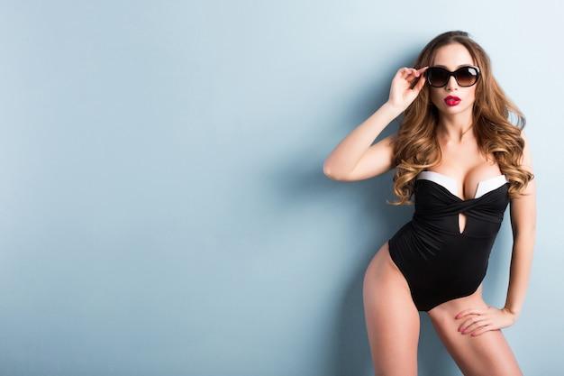 Brunette tan girl wearing swimsuit and sunglasses.