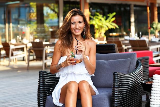 Bella donna bruna abbronzata che si rilassa e si diverte nella terrazza del ristorante dell'hotel
