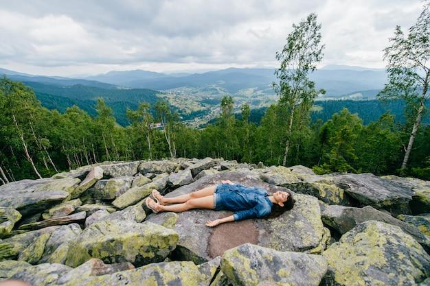 山の上に石の上に横たわるブルネットの十代の少女