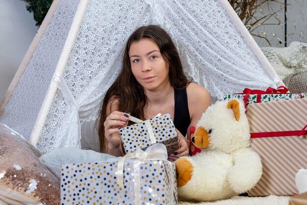 크리스마스 선물 상자와 장난감 사이에 누워 갈색 머리 십 대 소녀