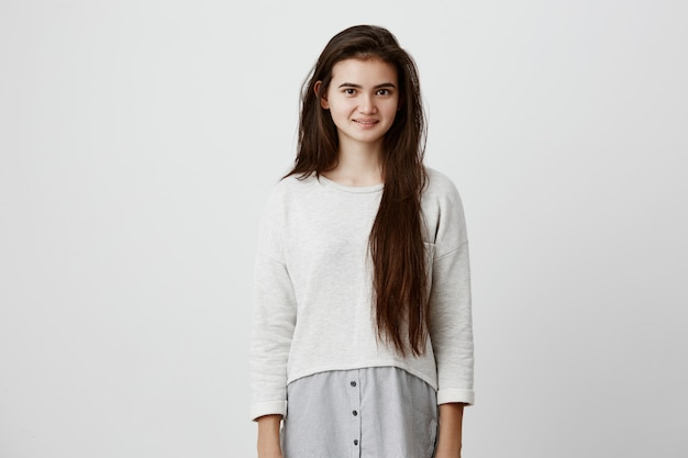 Брюнетка подростковой носить длинные волосы распущенные в повседневной одежде, радостно улыбаясь