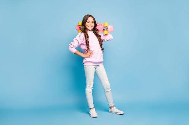Brunette teenager posing against the blue wall