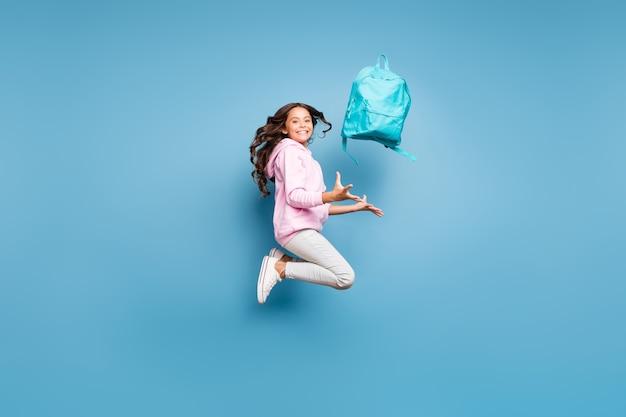青い壁に対してポーズをとるブルネットのティーンエイジャー