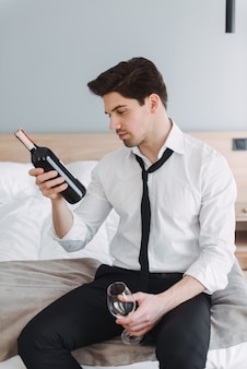 호텔 아파트에서 침대에 앉아있는 동안 와인과 유리 병을 들고 공식적인 옷을 입고 갈색 머리 생각 사업가