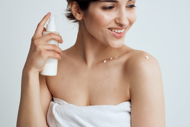 Brunette in towel with lotion moisturizing clean skin spa treatments