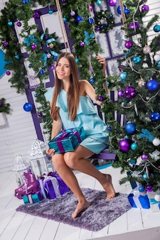 Brunette in a turquoise dress sitting on a swing next to a chrismas