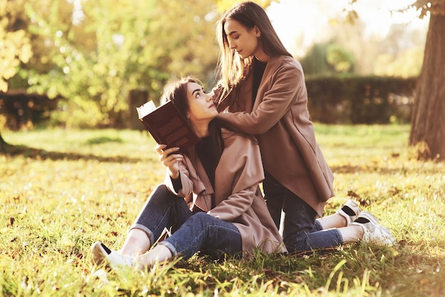 Brunette twin girls sitting on the grass and looking at each other. one of them is holding brown book, onother one is leaning on sisters shoulders from the back in autumn park on blurry background.