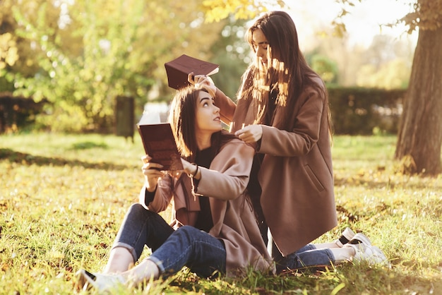 Brunette twin girls sitting on the grass with brown books in hands and looking at each other, when one of them is standing on her knees near the back of her sister in autumn park on blurry background.