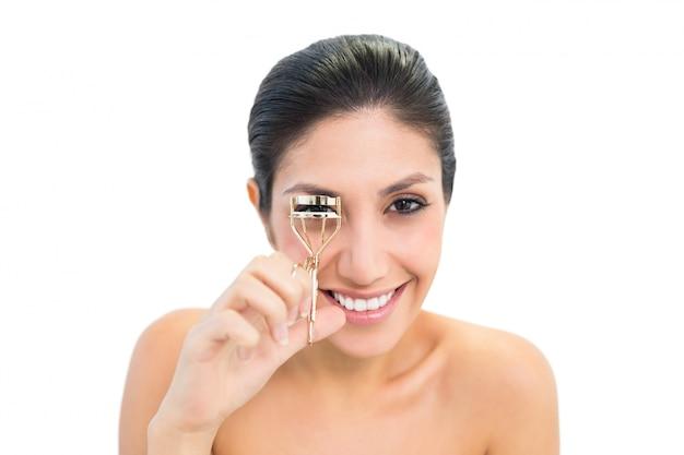 Brunette using eyelash curler and smiling at camera