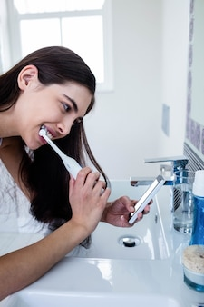 Brunette using smartphone while brushing teeth in bathroom