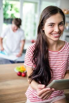 Brunette using tablet in kitchen and her boyfriend ironing