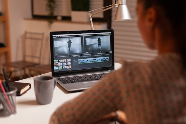 Brunette video editor works with footage on personal laptop in home ktichen during night time. content creator in home working on montage of film using modern software for editing late at night.