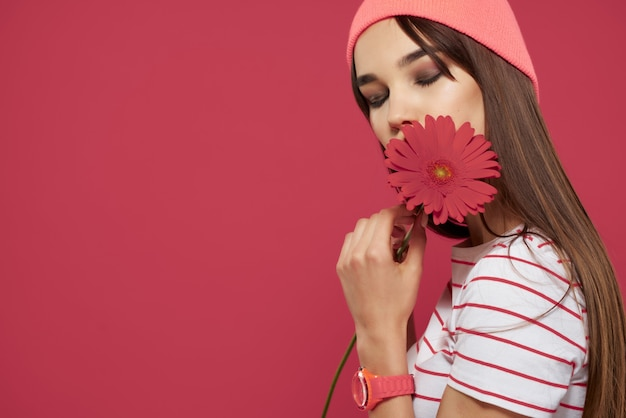 ピンクの帽子をかぶっているブルネット赤い花の化粧の装飾ピンクの背景