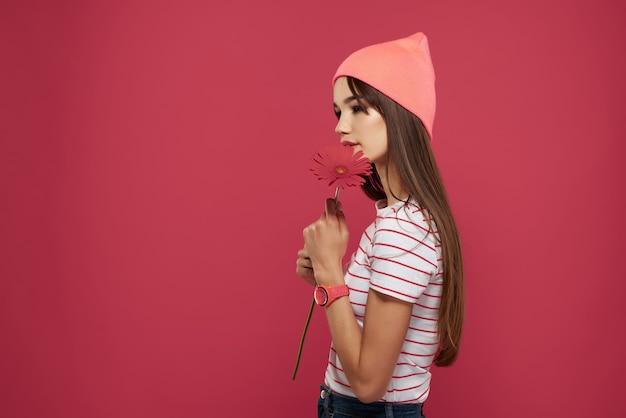 ピンクの帽子の赤い花の化粧の装飾を身に着けているブルネット