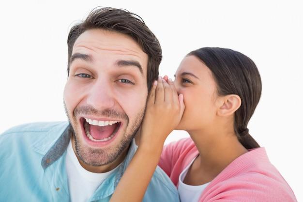 Brunette whispering secret to her boyfriend
