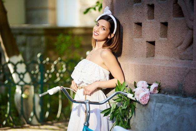 Brunette in white dress leans on red old building wall with her blue vintage bike