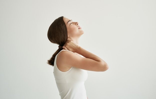 Brunette in white tshirt joint pain health problems dissatisfaction