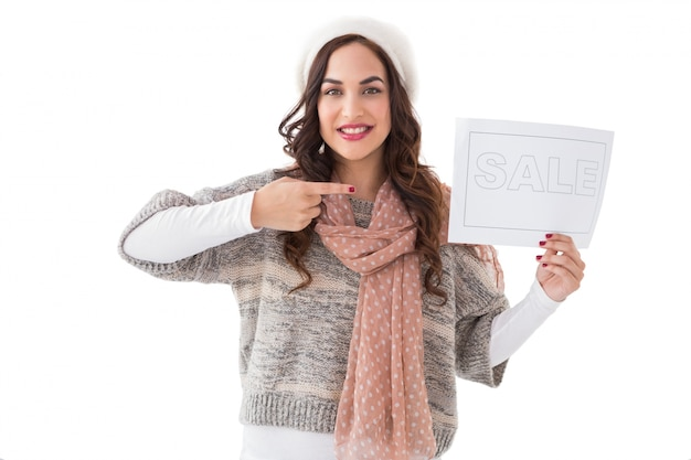 Brunette in winter clothes showing sale sign