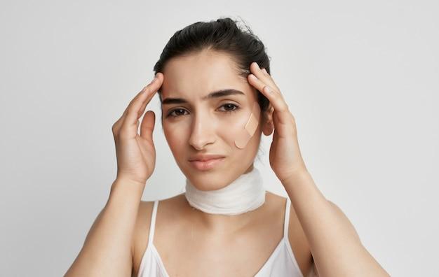 Брюнетка с перевязанной шеей держит ее проблемы со здоровьем